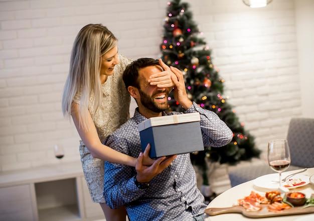 Giovane che ottiene presente dalla donna amorevole per natale o capodanno Foto Premium