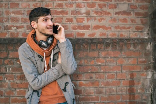 Giovane che parla al telefono all'aperto. Foto Premium