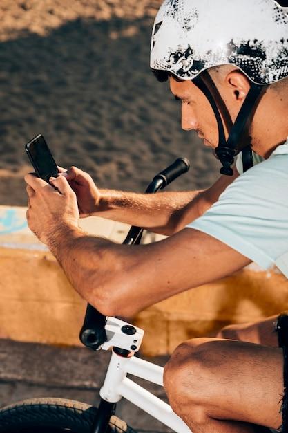 Giovane che per mezzo dello smart phone sulla sua bici Foto Gratuite