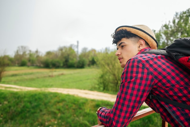 Giovane che porta cappello portando zaino guardando lontano Foto Gratuite