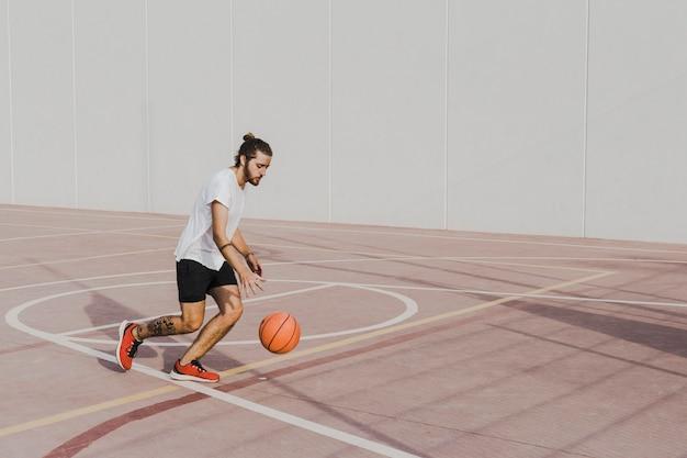 Giovane che pratica pallacanestro nella corte all'aperto Foto Gratuite