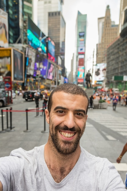 Giovane che prende selfie a times square Foto Premium