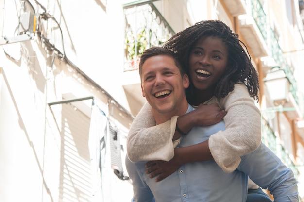 Giovane che ride e che porta la ragazza sul retro all'aperto Foto Gratuite