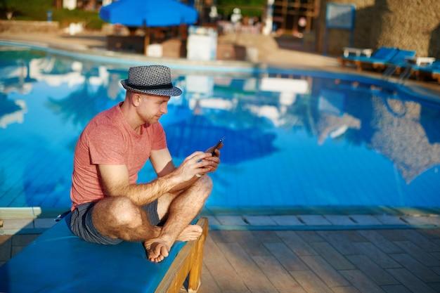 Giovane che riposa sulle chaise-lounge del sole Foto Premium