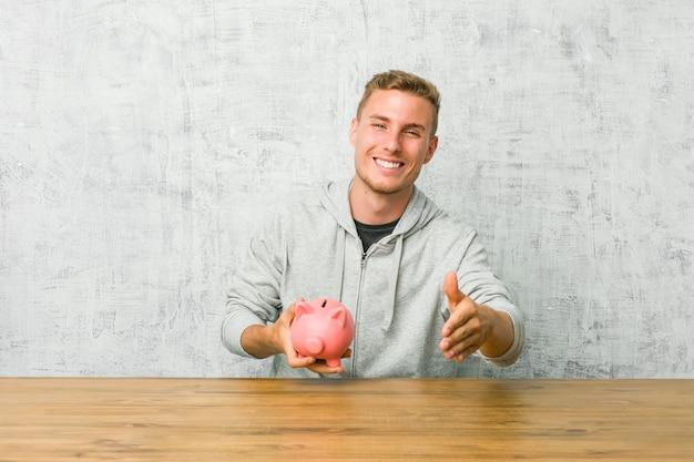 Giovane che risparmia soldi con un porcellino salvadanaio che allunga mano alla macchina fotografica nel gesto di saluto. Foto Premium