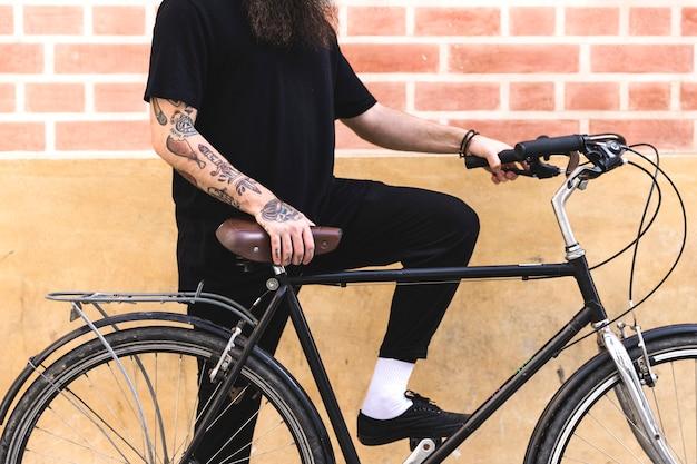 Giovane che si leva in piedi con la bicicletta contro la parete Foto Gratuite