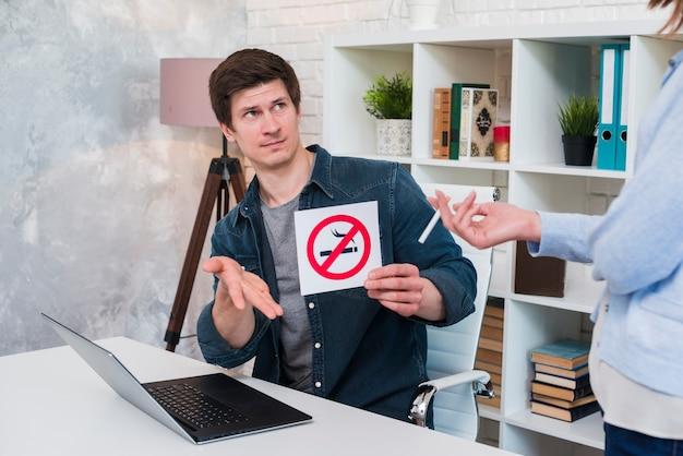 Giovane che si siede nell'ufficio che mostra segno non fumatori alla sigaretta della tenuta della donna Foto Gratuite
