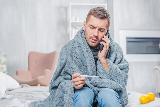 Giovane che si siede sul letto avvolto in sciarpa guardando il termometro parlando sul telefono cellulare Foto Gratuite
