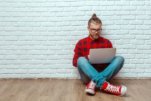 Giovane che si siede sul pavimento con il computer portatile Foto Premium