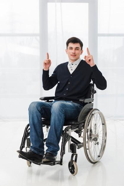 Giovane che si siede sulla sedia a rotelle che mostra il suo dito verso l'alto che guarda l'obbiettivo Foto Gratuite