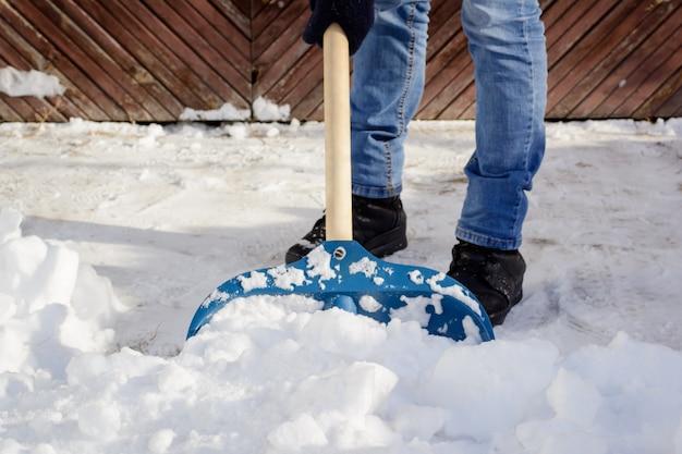 Giovane che spala neve nella strada privata vicino al garage Foto Premium