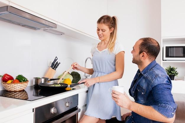 Giovane che tiene in mano la tazza di caffè che esamina sua moglie sorridente che cucina alimento nella cucina Foto Gratuite