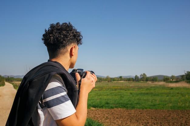 Giovane che tiene la macchina fotografica digitale moderna Foto Gratuite