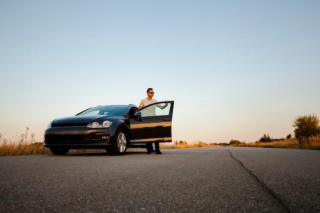 Giovane che tiene la portiera della macchina Foto Gratuite