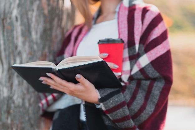 Giovane che tiene un libro nella foresta Foto Gratuite