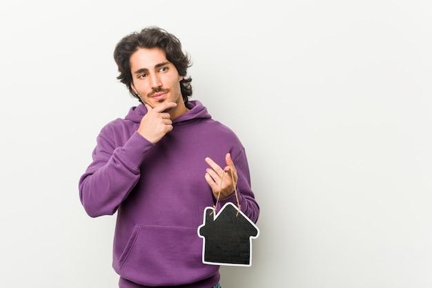 Giovane che tiene una forma dell'icona della casa che guarda lateralmente con l'espressione dubbiosa e scettica. Foto Premium