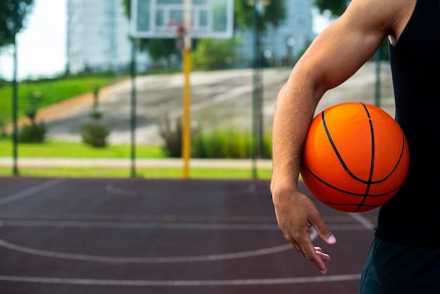 Giovane che tiene una palla sul campo Foto Gratuite