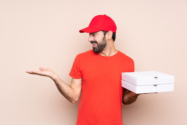Giovane che tiene una pizza con la mano estesa Foto Premium