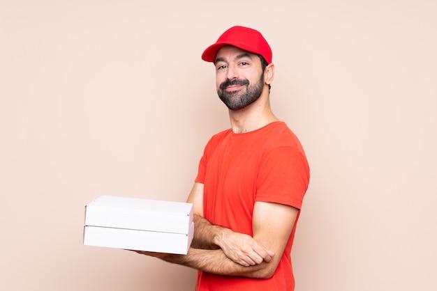 Giovane che tiene una pizza con le braccia attraversate e che osserva in avanti Foto Premium