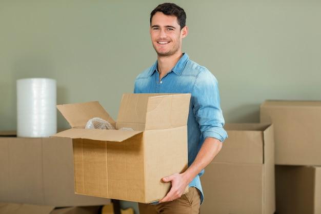 Giovane che trasportano scatole di cartone nella sua nuova casa Foto Premium