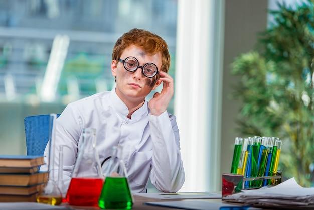 Giovane chimico pazzo che lavora in laboratorio Foto Premium