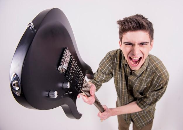 Giovane chitarrista con la chitarra elettrica in studio. Foto Premium