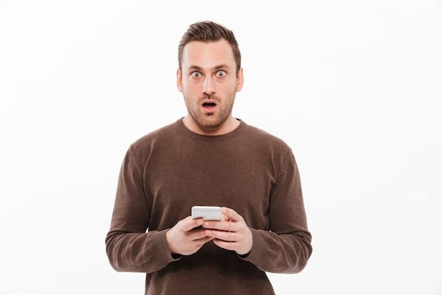Giovane colpito che chiacchiera dal telefono cellulare Foto Gratuite