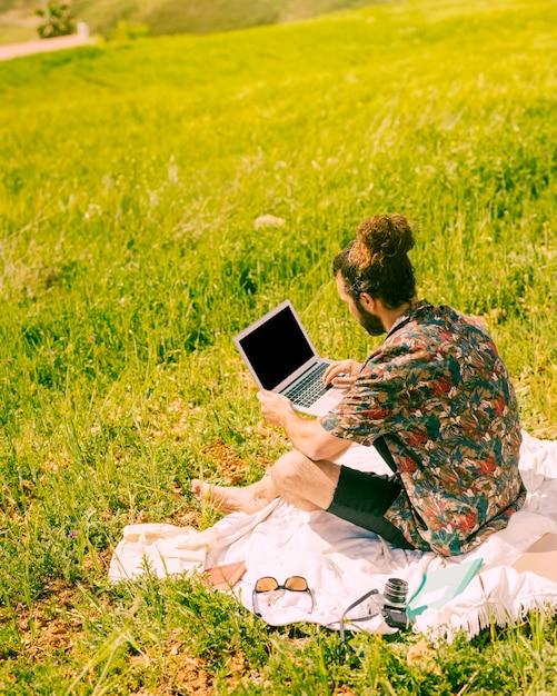 Giovane computer portatile della tenuta dell'uomo della brunetta sulla natura Foto Gratuite