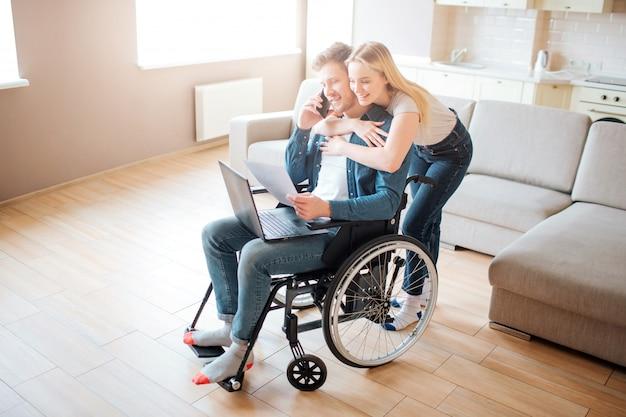 Giovane con bisogni speciali. seduto sulla sedia a rotelle e parlando al telefono. la giovane donna lo abbraccia. in piedi da dietro. laptop in ginocchio. Foto Premium