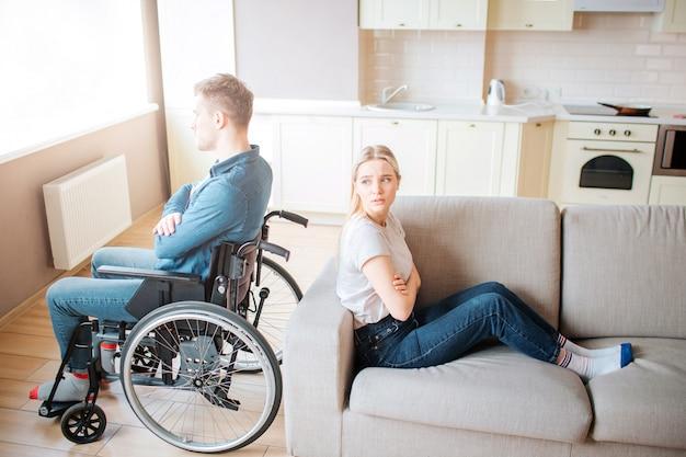Giovane con disabilità sedersi sulla sedia a rotelle e guardare la finestra. discutere e quirrel. ragazzo con bisogni speciali seduto schiena contro schiena con la fidanzata. la giovane donna prova a guardarlo. Foto Premium