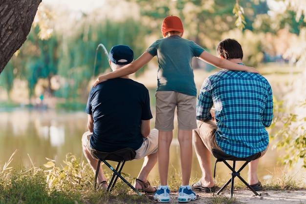 Giovane con figlio e padre pesca sul fiume. Foto Premium