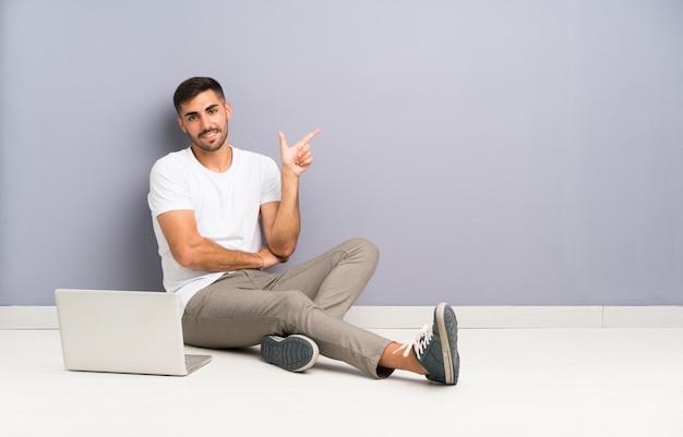 Giovane con il suo laptop seduto uno sul pavimento che punta il dito verso il lato Foto Premium