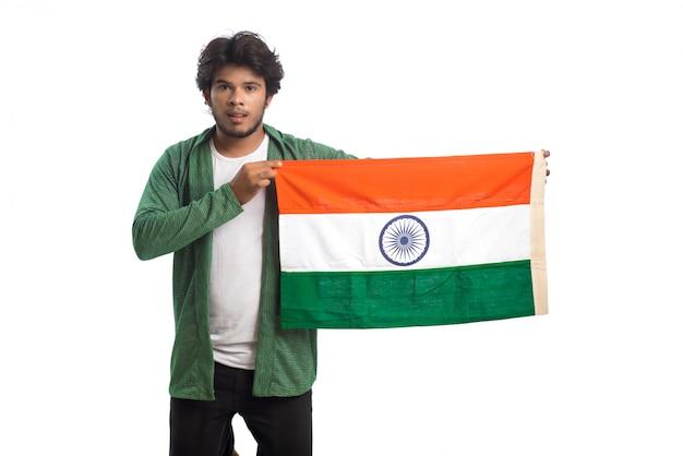 Giovane con la bandiera indiana o tricolore su fondo bianco, festa dell'indipendenza indiana, festa della repubblica indiana Foto Premium
