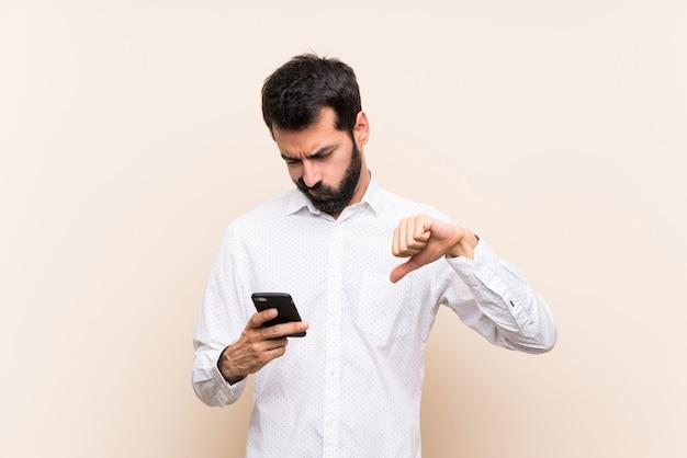 Giovane con la barba che tiene un cellulare che mostra pollice giù Foto Premium