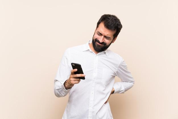 Giovane con la barba che tiene un cellulare che soffre di mal di schiena per aver fatto uno sforzo Foto Premium