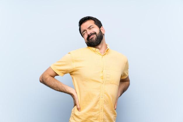 Giovane con la barba sopra isolato blu che soffrono di mal di schiena per aver fatto uno sforzo Foto Premium