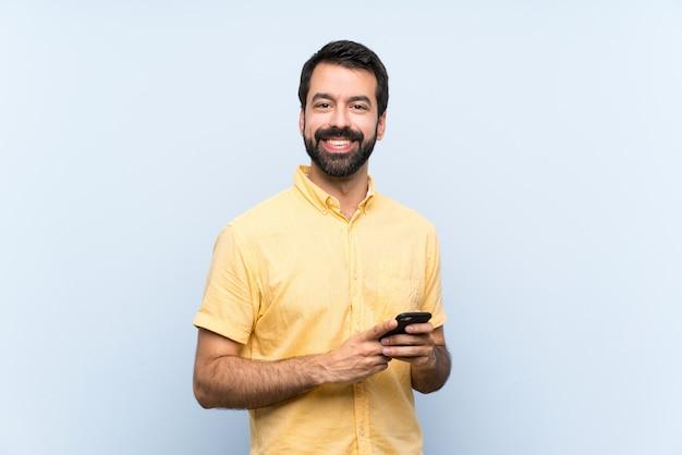Giovane con la barba sul blu che invia un messaggio con il cellulare Foto Premium