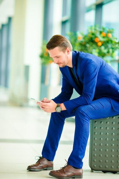 Giovane con lo smart phone in aeroporto. uomo caucasico con il cellulare all'aeroporto mentre aspettando l'imbarco Foto Premium