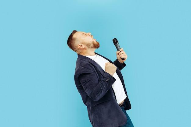 Giovane con microfono sulla parete blu Foto Gratuite