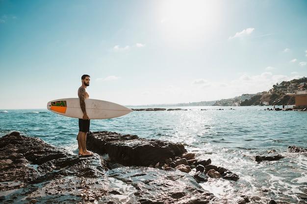 Giovane con tavola da surf su pietra vicino all'acqua Foto Gratuite