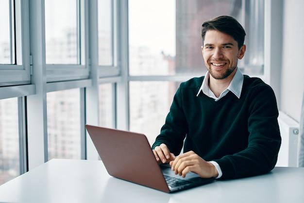 Giovane con un computer portatile in un tailleur lavorando in ufficio ea casa sullo sfondo di una finestra, intervistando online Foto Premium