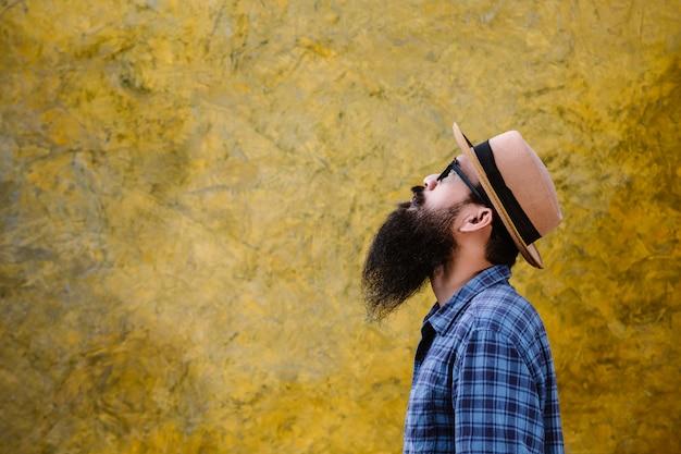 Giovane con una lunga barba che indossa un cappello e occhiali Foto Gratuite