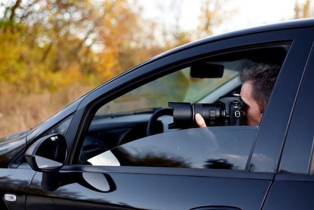 Giovane con una macchina fotografica del dslr in un'automobile Foto Premium