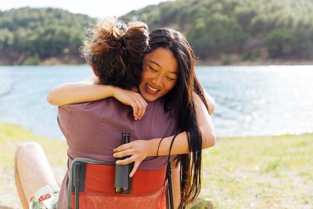 Giovane coppia abbracciando sulla riva del fiume Foto Gratuite
