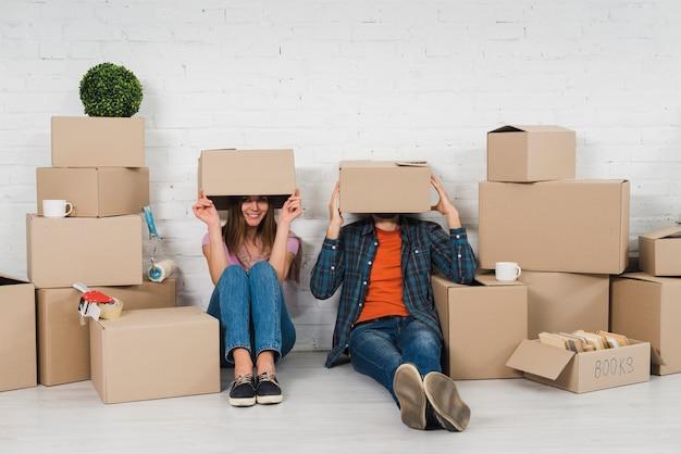 Giovane coppia che nasconde il viso tra le scatole di cartone nella loro nuova casa Foto Gratuite