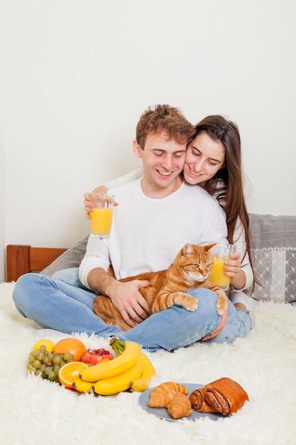 Giovane coppia facendo colazione a letto Foto Gratuite