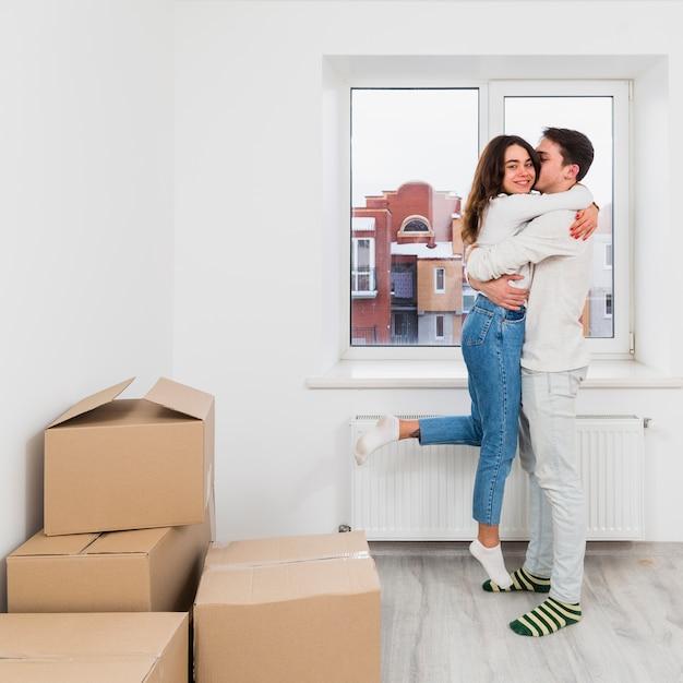 Giovane coppia godendo nella loro nuova casa con scatole di cartone Foto Gratuite