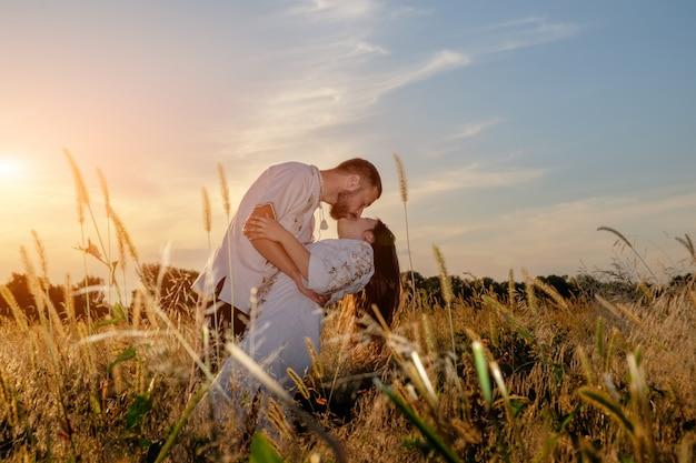 Giovane coppia in abiti tradizionali abbracciare e baciare in campo Foto Premium