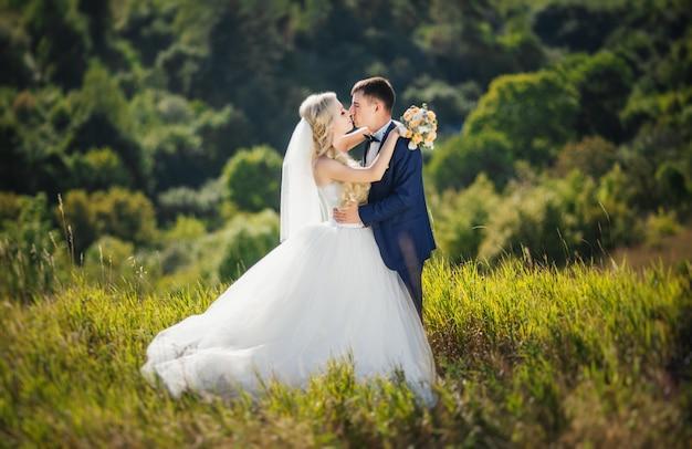 Giovane coppia in amore, lo sposo e la sposa in abito da sposa baciare la natura. Foto Gratuite