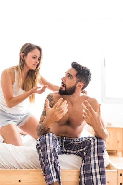 Giovane coppia litigare sul letto in camera da letto Foto Gratuite